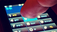 Fingers on smartphone keypad