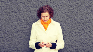 Woman leaning on wall using smartphone